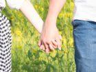 お花畑で恋人つなぎをするカップル