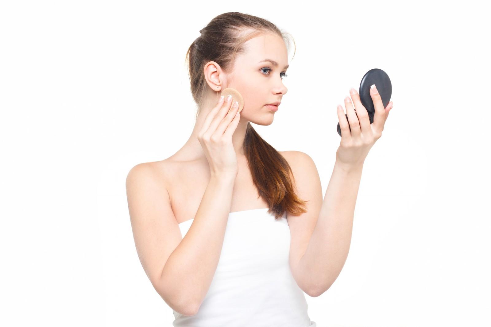 コンパクトミラーを見ながら真剣な表情で化粧をする女性
