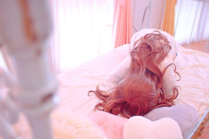 二日酔いでベッドでうなだれている女の子の画像