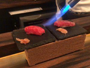 ーナーで炙られている肉寿司