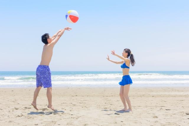 浜辺で楽しそうにビーチーボールで遊んでいるカップル