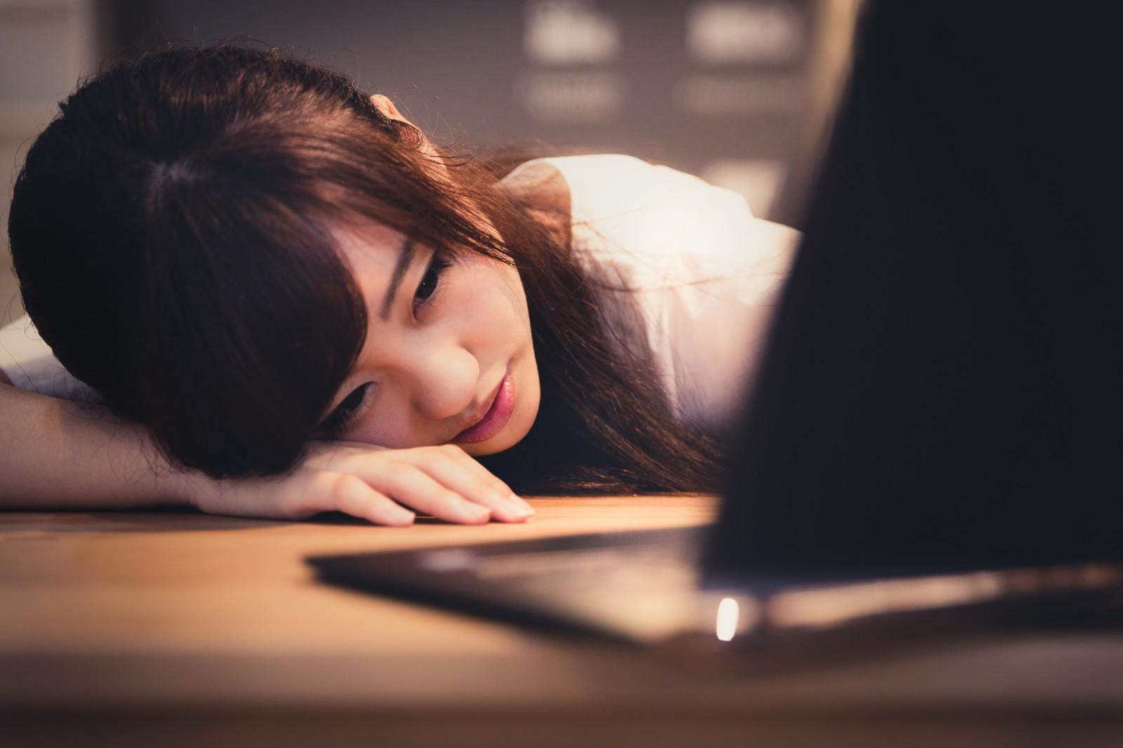 パソコンの前でぐったりする女性の画像