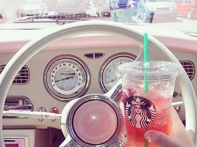 運転席でスタバを飲んでいる画像