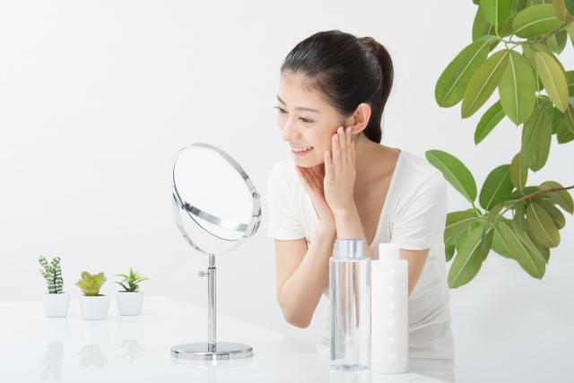 鏡でお肌状態をチェックする綺麗な女性