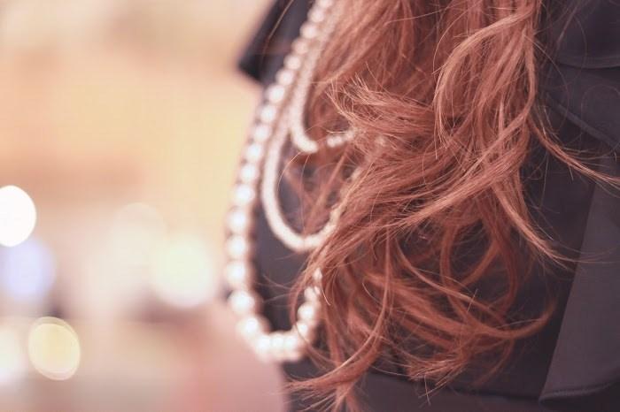 コテで髪の毛を巻いた女性の画像