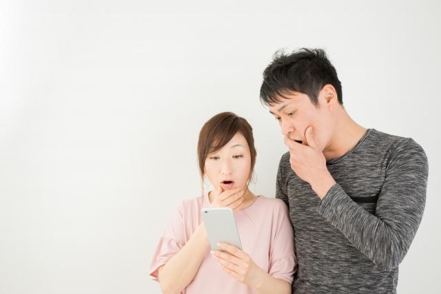 携帯をみて驚くカップルの画像