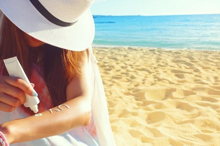 海辺で日焼け止めを塗る女の子の画像