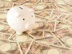 たくさんの1万円札の上に豚の貯金箱