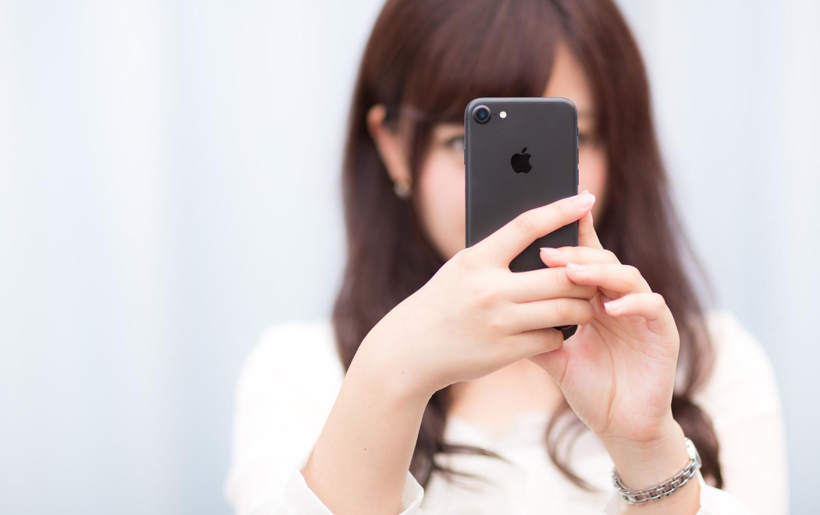 マットブラックカラーのスマートフォンを操作する女性
